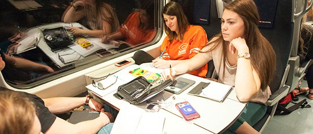 Female Carroll students writing while traveling on a train