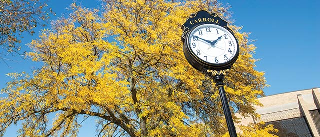 clock with a tree in full fall color behind