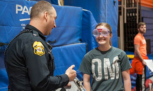 Student in drunk goggles talking to a police officer