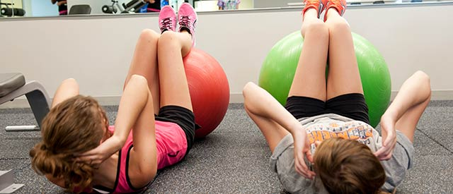 two female students doing crunches using exercise balls