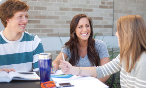 three students sharing a laugh while studying